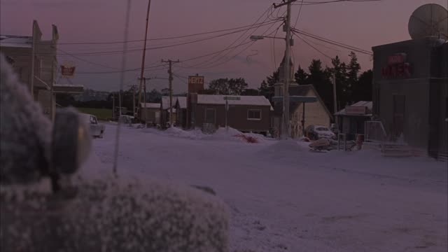 WIDE ANGLE OF SMALL TOWN. STREETS, SIDEWALKS COVERED IN SNOW. DINER, CHURCH, GENERAL STORE VISIBLE. SNOW BANKS ON SIDEWALKS, ONE STAINED WITH BLOOD. TELEPHONE POLES AND SATELLITE DISHES VISIBLE ABOVE BUILDINGS. GREEN FIELD IN BG. FROSTED CAR IN FOREGROUND