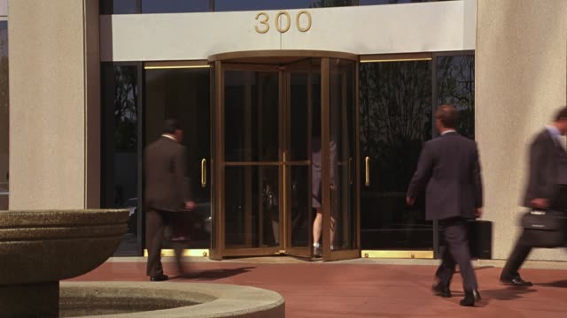 "vídeos y material grabado en eventos de stock de wide angle of businessmen and businesswomen entering and exiting business office building ""300"" through revolving door.  empty water fountain. business people. camera pans up multi- story building with glass windows. 8 fps - puerta giratoria"