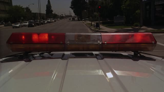 vídeos y material grabado en eventos de stock de wide angle driving pov atop  police car with flashing sirens or bizbar driving on suburb street.  cars. police car stops in traffic and makes a left onto florence blvd in downey, california. - coche de policía