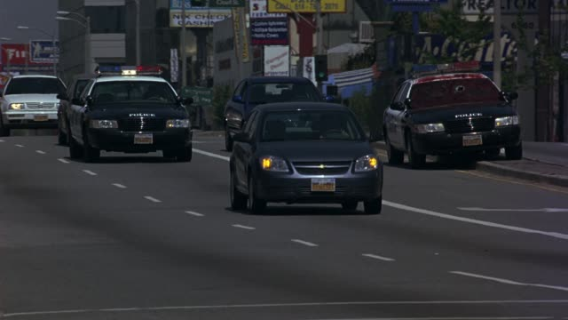 pan left to right of cars driving along los angeles city street. police car chasing police car with foot and leg through front windshield. blood or red substance dried on glass. weaving through traffic. car chases. police chases. - パトカー点の映像素材/bロール