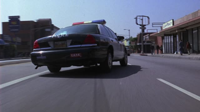 wide angle moving pov  bumpercam of police car swerving through cars driving on city streets. car chases. police chases. - パトカー点の映像素材/bロール