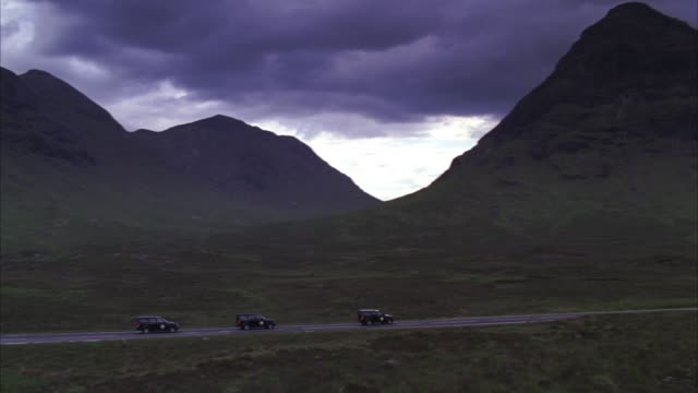 pan left to right of three land rover suvs driving on mountain road through rolling green hills and mountain peaks of scottish landscape. low dark clouds hang over mountains. cloudy and overcast. could be before storm or rain. motorcade. - springtime stock videos & royalty-free footage