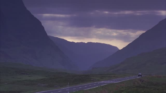 pull back of land rover suv driving on mountain road through rolling green hills and mountain peaks of scottish landscape. low dark clouds hang over mountains. cloudy and overcast. could be before storm or rain. could be late afternoon or sunset. - hill stock videos & royalty-free footage