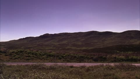 wide angle of three land rover suvs driving on two lane road through countryside of scottish landscape. motorcade. - sports utility vehicle bildbanksvideor och videomaterial från bakom kulisserna