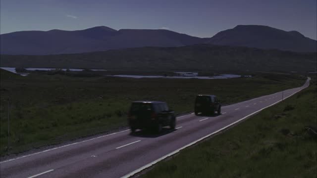stockvideo's en b-roll-footage met wide angle of three land rover suvs driving on two lane road through countryside of scottish landscape. rolling hills and mountain peaks. motorcade. - sports utility vehicle