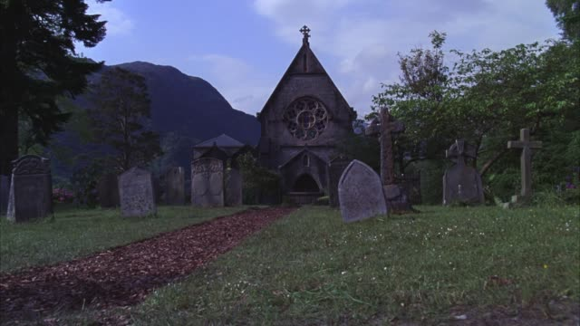 pan up of man riding horse along mulch path through cemetery with tombstones or gravestones. graveyard outside 19th century scottish landmark, catholic church of st. mary and st. finnan. gothic architecture chapel with steeple, arched doorways and rose wi - gothic stock videos & royalty-free footage
