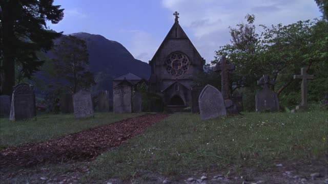 pan up of man riding horse along mulch path through cemetery with tombstones or gravestones. graveyard outside 19th century scottish landmark, catholic church of st. mary and st. finnan. gothic architecture chapel with steeple, arched doorways and rose wi - chapel stock videos & royalty-free footage