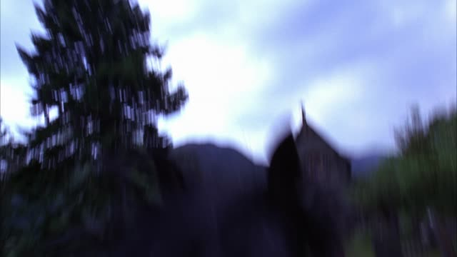 hand held moving pov from rider of horse of cemetery with tombstones or gravestones. graveyard outside 19th century scottish landmark, catholic church of st. mary and st. finnan. gothic architecture chapel with steeple, arched doorways and rose window sur - chapel stock videos & royalty-free footage