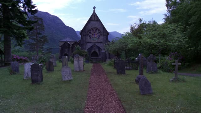 hand held moving pov of cemetery with tombstones or gravestones. graveyard outside 19th century scottish landmark, catholic church of st. mary and st. finnan. gothic architecture chapel with steeple, arched doorways and rose window surrounded by lush tree - chapel stock videos & royalty-free footage