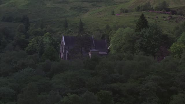 wide angle of 19th century scottish landmark, catholic church of st. mary and st. finnan. gothic architecture chapel surrounded by lush trees and rolling hills. beauty shot. - chapel stock videos & royalty-free footage