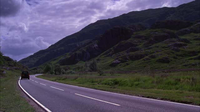 wide angle of scottish mountains and hills alongside two lane road. black land rover suv is seen driving on road. - mountain range stock videos & royalty-free footage