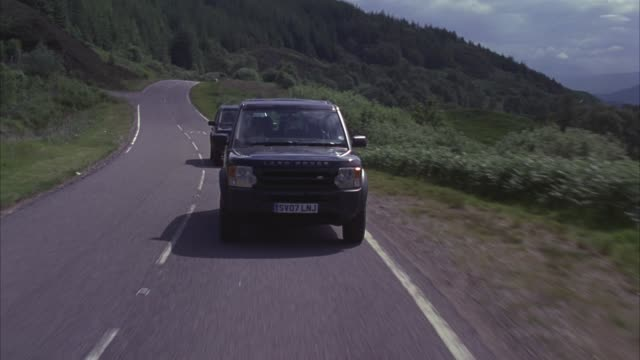 process plate straight back of land rover suvs driving on two lane road through scottish highlands. hills and mountains in bg. matching plates 3238-008 to 3238-017. - land rover stock videos & royalty-free footage