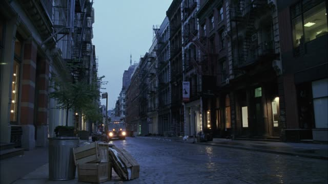 pan left to right across a cobblestone street in soho.  a garbage truck drives through the cast iron buildings which hold galleries and boutiques. early morning. - ゴミ収集車点の映像素材/bロール