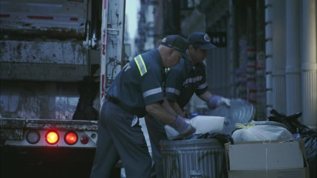 vidéos et rushes de medium angle of two garbage men loading garbage into the back of a garbage truck in soho. - camion poubelles