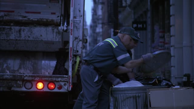 medium angle of two garbage men loading garbage into the back of a garbage truck in soho. trash collection. - ゴミ収集車点の映像素材/bロール
