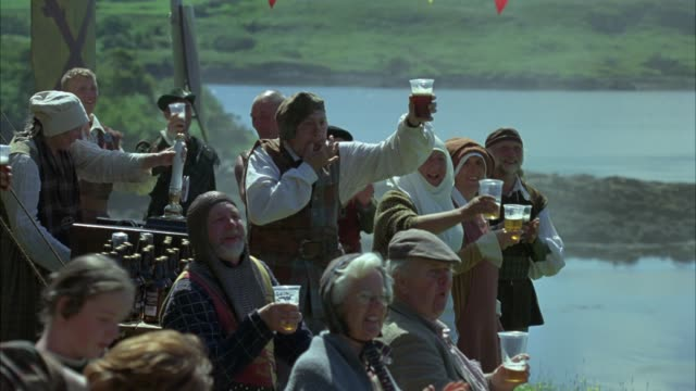 zoom in on highland or scottish games festivities. spectators or cheering crowd drinking beer and wearing traditional medieval costumes. could be renaissance fair or cultural fair. tent, flags, lake or loch and rolling hills in bg. - beer alcohol stock videos & royalty-free footage