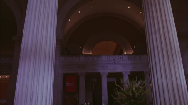 WIDE ANGLE OF PEOPLE OR TOURISTS ENTERING AND EXITING ENTRANCE TO METROPOLITAN MUSEUM OF ART IN NEW YORK. MUSEUM HAS PILLAR COLUMNS.
