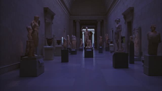 WIDE ANGLE OF HALLWAY IN MUSEUM WITH ANCIENT GREEK OR ROMAN SCULPTURES, STATUES, AND POTTERY FROM  METROPOLITAN ART MUSEUM IN NEW YORK. GALLERIES.