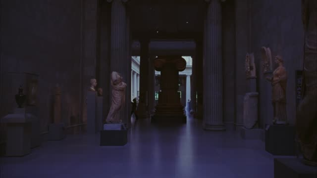 WIDE ANGLE OF HALLWAY IN MUSEUM WITH ANCIENT GREEK OR ROMAN SCULPTURES, STATUES, AND POTTERY FROM  METROPOLITAN ART MUSEUM IN NEW YORK. GALLERIES.  IONIC COLUMNS.