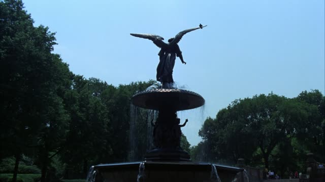 vídeos de stock e filmes b-roll de medium angle of angel of the waters fountain at bethesda fountain in central park, new york. trees. - fonte bethesda
