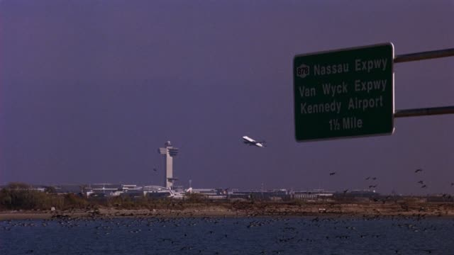 """wide angle of airplane take-off at jfk airport. air traffic control tower and airport terminals visible in bg. highway """"878 nassau expwy, van wyck expwy, and kennedy airport 1 1/2 mile"""" sign in fg. geese are flying over water. - flughafen kontrollturm stock-videos und b-roll-filmmaterial"""