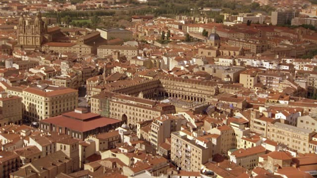 AERIAL OF SALAMANCA, SPAIN. CLUSTER OF MULTI-STORY BUILDINGS WITH RED TILE ROOFS WITH SPANISH LANDMARKS: PLAZA MAYOR SQUARE, LA CLERECIA CHURCH, UNIVERSITY OF SALAMANCA AND LA CATEDRAL NUEVA CATHEDRAL. CITYSCAPES. EUROPE.