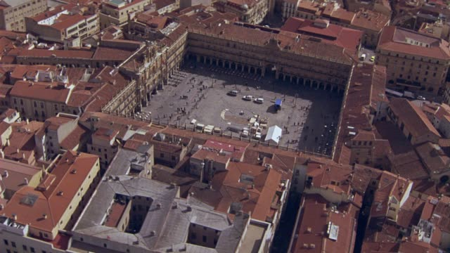AERIAL OF SALAMANCA, SPAIN WITH SPANISH LANDMARK, PLAZA MAYOR SQUARE. CLUSTER OF MULTI-STORY BUILDINGS WITH RED TILE ROOFS. CITYSCAPES. EUROPE.