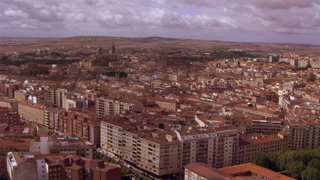 AERIAL OF SALAMANCA, SPAIN FOLLOWING RAILROAD TRACKS INTO DOWNTOWN. CLUSTER OF MULTI-STORY BUILDINGS WITH RED TILE ROOFS WITH SPANISH LANDMARKS: ALAMEDILLA PARK, PLAZA MAYOR SQUARE, LA CLERECIA CHURCH, UNIVERSITY OF SALAMANCA AND LA CATEDRAL NUEVA CATHEDR