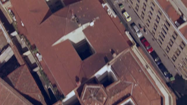 AERIAL BIRDSEYE POV OF MULTI-STORY BUILDINGS WITH RED TILE ROOFS, INTERSECTIONS AND CARS DRIVING ON CITY STREETS OF SALAMANCA, SPAIN. EUROPE.