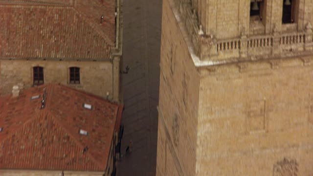 AERIAL BIRDSEYE POV OF MULTI-STORY BUILDINGS WITH RED TILE ROOFS AND PEDESTRIANS OR PEOPLE WALKING ON CITY STREETS OF SALAMANCA, SPAIN.  COULD BE AERIAL SEARCH PARTY. EUROPE.