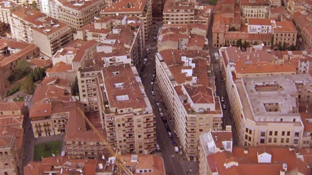 AERIAL OF CARS AND PEDESTRIANS OR PEOPLE WALKING ALONG CITY STREETS BETWEEN MULTI-STORY BUILDINGS WITH RED TILE ROOFS OF SALAMANCA, SPAIN. EUROPE. CONSTRUCTION CRANE IN FG.