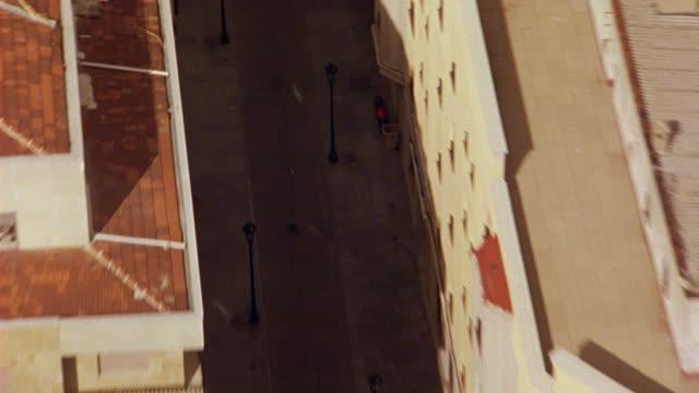 vídeos y material grabado en eventos de stock de aerial of city street between multi-story buildings with red tile roofs of salamanca, spain. europe. zooms in. could be aerial search party. - salamanca