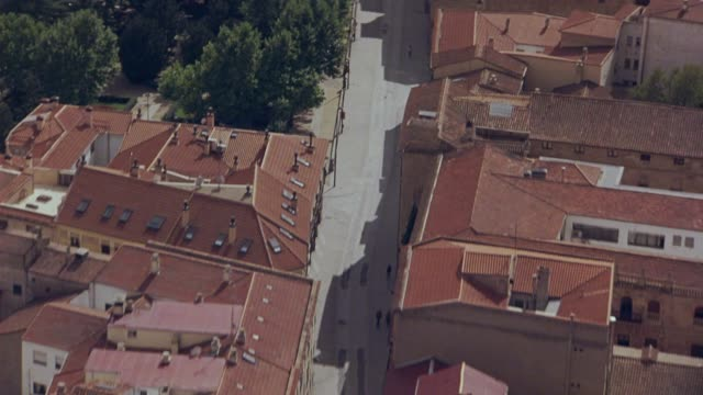 vídeos y material grabado en eventos de stock de aerial of multi-story buildings with red tile roofs and city streets of salamanca, spain. cars driving over bridge over river, rio tormes, towards traffic circle or roundabout with monument. europe. - salamanca