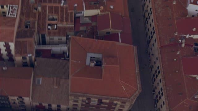 vídeos y material grabado en eventos de stock de aerial birdseye pov of cars on city street between multi-story buildings with red tile roofs of salamanca, spain. europe. could be aerial search party. - salamanca