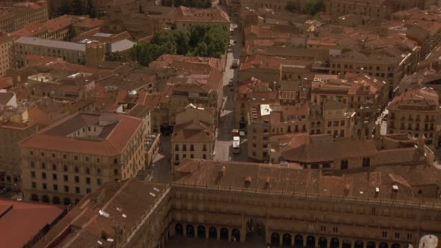 aerial of spanish landmark, plaza mayor square, multi-story buildings with red tile roofs and city streets of salamanca, spain. cars driving over bridge over river, rio tormes, towards traffic circle or roundabout with monument. europe. - stockwerk stock-videos und b-roll-filmmaterial
