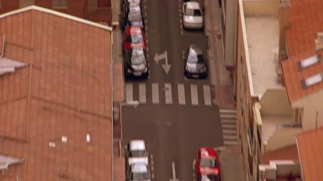 AERIAL OF CARS AND PEDESTRIANS OR PEOPLE WALKING ALONG CITY STREETS BETWEEN MULTI-STORY BUILDINGS WITH RED TILE ROOFS OF SALAMANCA, SPAIN. EUROPE.