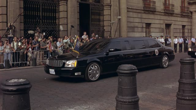 wide angle of cadillac deville limo with presidential seal parked on stone street outside plaza mayor in salamanca, spain. press and reporters gathered behind stanchions with microphones, boom mics, cameras and video cameras. waiting for american presiden - limousine stock videos & royalty-free footage