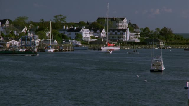 vídeos de stock e filmes b-roll de pan up from ocean to boats, sailboats and docks in harbor. ferry. shingle style upper class vacation houses along waterfront. edgartown, martha's vineyard. new england. coastal town. - embarcação comercial