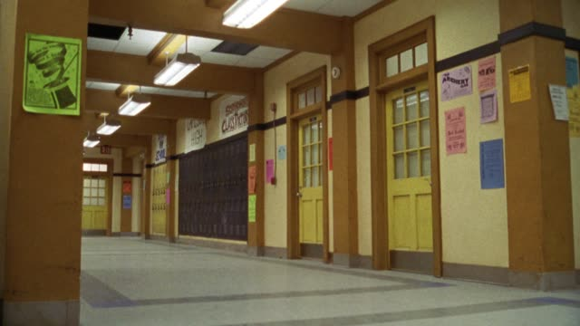wide angle of high school hallway. classroom doors open and students and teachers, people walk out of classrooms into hallway. - 廊下点の映像素材/bロール