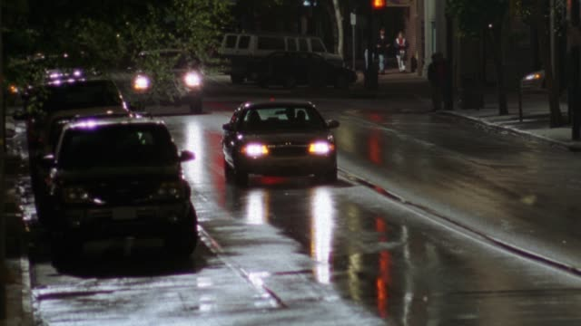 wide angle of a car driving towards camera on a wet, tree-lined, two lane road. could be downtown in a small town. car does a u-turn in middle of the road then drives away from camera. - ノースカロライナ州点の映像素材/bロール