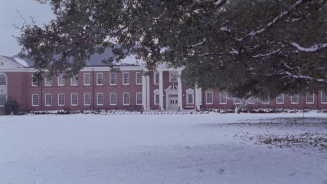 wide angle of two story brick building built in colonial greek revival style with white columns. ground is covered in snow. tree braches in fg partially block view of building. could be on a college campus. - zweistöckiges bauwerk stock-videos und b-roll-filmmaterial