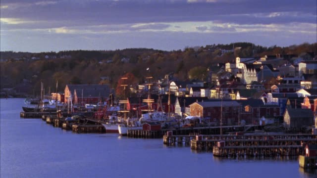 wide angle of seaside port town with hills in bg. see docks, some with small boats anchored. see many multi-story buildings, could be houses, businesses, schools, or churches. see ocean or other large body of water. could be halifax. coastal town. could b - other stock videos & royalty-free footage
