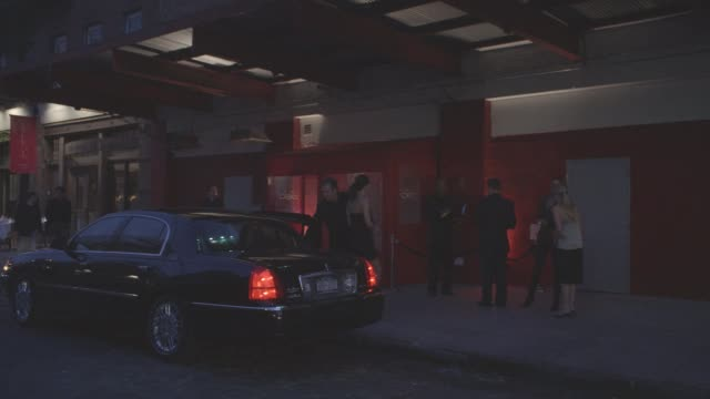 WIDE ANGLE OF CIELO NIGHTCLUB. MEN AND WOMEN STAND OUTSIDE CLUB WAITING IN LINE. ONE MAN ESCORTS A WOMAN FROM A LIMO PAST THE LINE AND INTO THE CLUB. BARS.