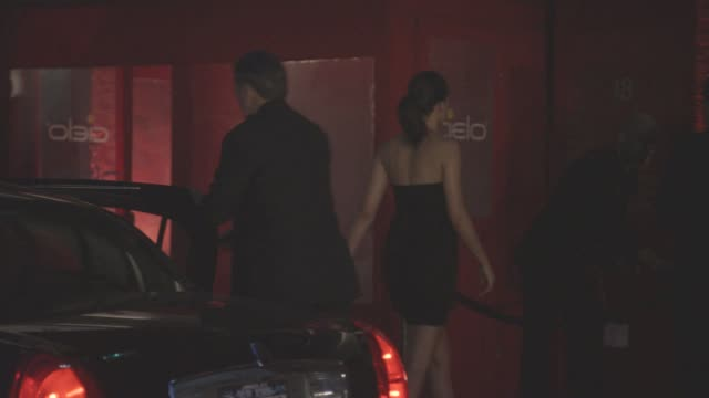 MEDIUM ANGLE OF CIELO NIGHTCLUB. MEN AND WOMEN STAND OUTSIDE CLUB WAITING IN LINE AND TALKING TO BOUNCER. ONE MAN ESCORTS A WOMAN FROM A LIMO PAST THE LINE  AND INTO THE CLUB. BARS.