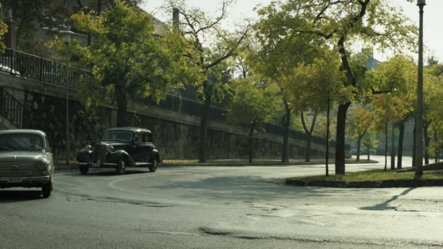PAN RIGHT TO LEFT OF TWO CLASSIC CARS, 1950 MERCEDES BENZ 170S CABRIOLET CAR, DRIVING AROUND CURVE IN STREET AND TOWARD MULTI-STORY BRICK BUILDINGS. EUROPE. TREE-LINED STREETS.