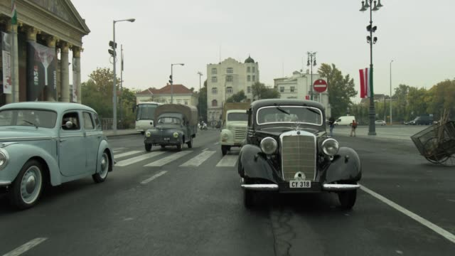 process plate straight back of 1950 mercedes benz 170s cabriolet car, classic cars driving on city street in budapest. europe. pass museum of fine arts. - budapest stock-videos und b-roll-filmmaterial