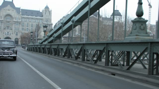 process plate 3/4 back right of classic cars driving across chain bridge over the river danube in budapest. pass lion capstones, multi-story buildings, gresham palace in bg. europe. budapest. cities. suspension bridge. - budapest stock videos & royalty-free footage