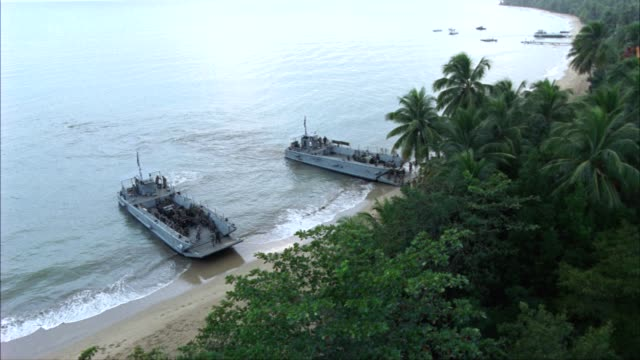 pan left to right along a long stretch of coastline.  two landing craft infantry or lci ships land on the beach, dumping out soldiers, jeeps, and trucks.  an amphibious assault.  supposed to be the bay of pigs, but could be used for wwii pacific campaign. - military land vehicle stock videos & royalty-free footage