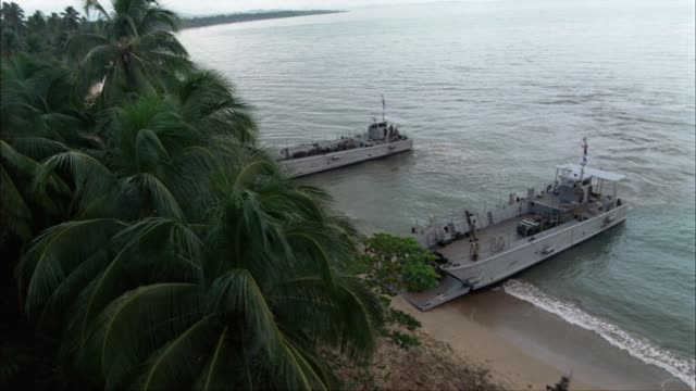 pan right to left along a long stretch of coastline.  two landing craft infantry or lci ships land on the beach, dumping out soldiers, jeeps, and trucks.  an amphibious assault.  supposed to be the bay of pigs, but could be used for wwii pacific campaign. - military land vehicle stock videos & royalty-free footage