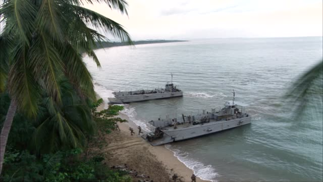 vidéos et rushes de pan right to left along a long stretch of coastline.  two landing craft infantry or lci ships land on the beach, dumping out soldiers, jeeps, and trucks.  an amphibious assault.  supposed to be the bay of pigs, but could be used for wwii pacific campaign. - véhicule militaire terrestre